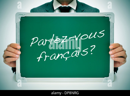 man wearing a suit holding a chalkboard with the question parlez-vous francais? do you speak french? written in - Stock Photo