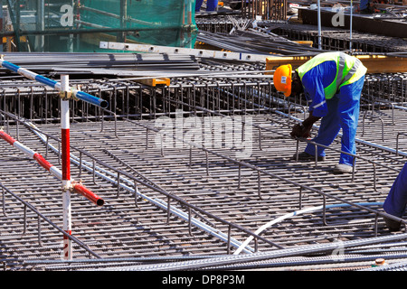 A steel fixer carefully tying reinforced steel bars in position in preparation for the construction of a concrete - Stock Photo