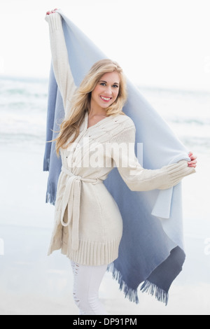 Delighted blonde woman shaking her blanket - Stock Photo