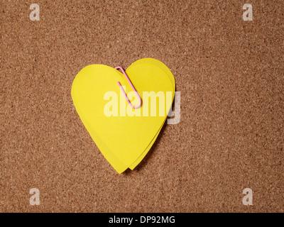 yellow heart shape sticky notes on cork board - Stock Photo