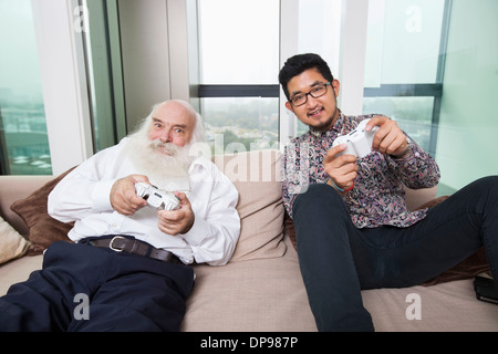 Portrait of grandson playing video game on sofa at home - Stock Photo