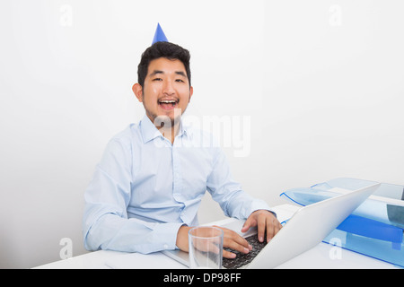 Portrait of happy businessman wearing party hat while working in office - Stock Photo