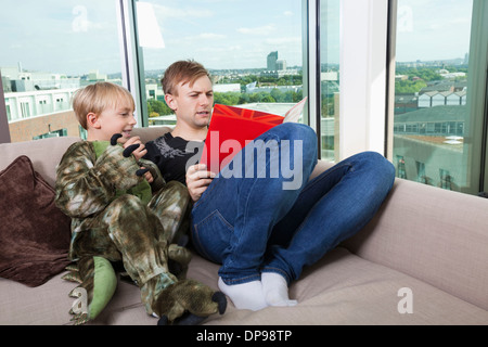 Boy dressed in dinosaur costume sitting with father reading story book on sofa bed at home - Stock Photo