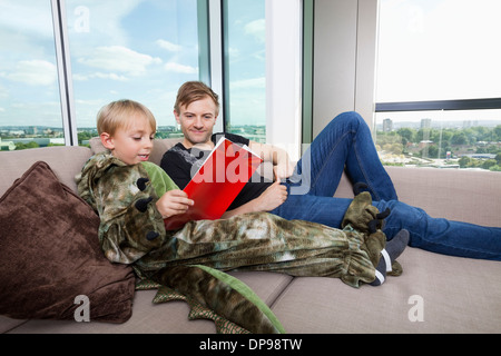 Boy dressed in dinosaur costume reading picture book with father on sofa bed at home - Stock Photo