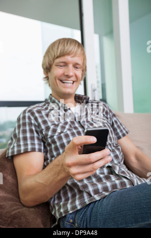 Cheerful mid-adult man text messaging on sofa at home - Stock Photo