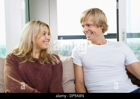 Cheerful couple sitting on sofa and looking at each other at home - Stock Photo