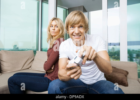 Angry woman looking at man play video game in living room at home - Stock Photo