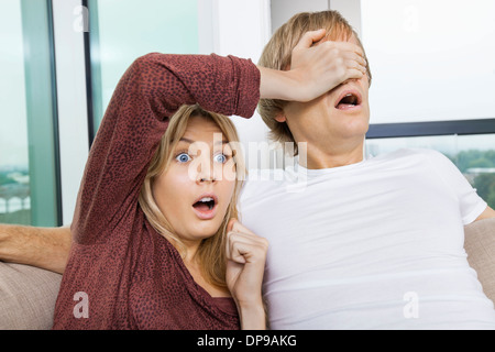 Shocked woman covering man's eyes while watching TV at home - Stock Photo