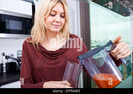 Young woman pouring carrot juice in glass at kitchen - Stock Photo