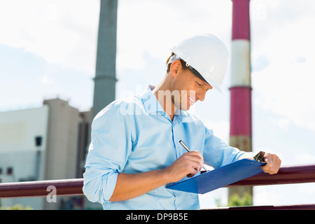 Male architect writing on clipboard at site - Stock Photo