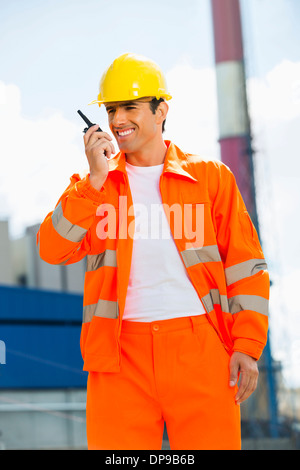 Happy architect wearing reflective workwear communicating on walkie-talkie at site - Stock Photo