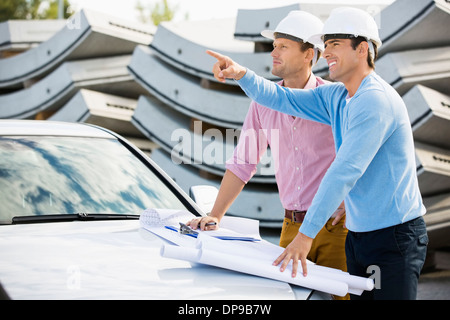 Architects with blueprints on car discussing at site - Stock Photo