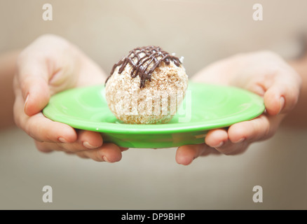 Human hands holding green plate with coconut cake - Stock Photo