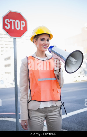 Smiling businesswoman wearing builders clothes shouting in megaphone - Stock Photo