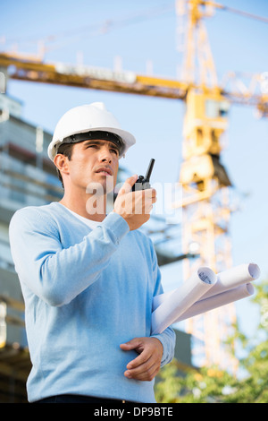 Male architect holding blueprints while using walkie-talkie at construction site - Stock Photo