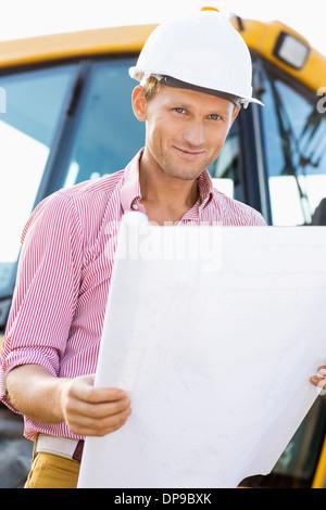 Portrait of male architect holding blueprint at construction site - Stock Photo