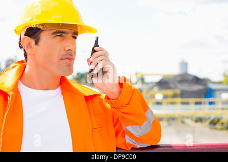 Male construction worker communicating on walkie-talkie at site - Stock Photo