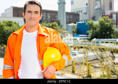 Portrait of male architect wearing reflective workwear at construction site - Stock Photo
