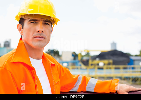 Portrait of handsome mid adult man wearing protective workwear at construction site - Stock Photo