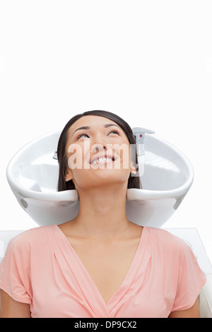 Woman resting head in sink against white background - Stock Photo