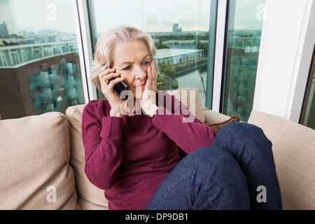 Worried senior woman answering smart phone on sofa at home - Stock Photo