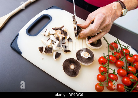 Senior woman's hand chopping mushrooms on cutting board - Stock Photo