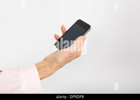 Businesswoman's hand holding smart phone in office - Stock Photo