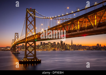 Twilight over the Oakland Bay Bridge with skyline of San Francisco beyond, California USA - Stock Photo