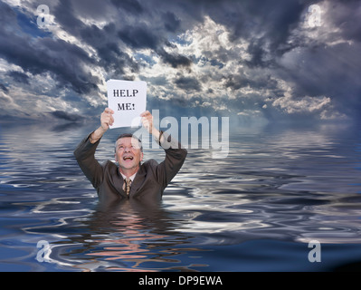 Concept image of senior businessman in suit in deep water drowning in paperwork with help me sign - Stock Photo