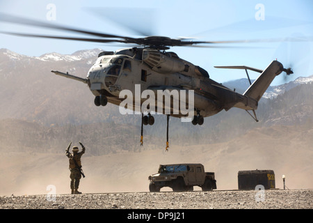 U.S. Marine directs the pilots of a CH-53E Super Stallion helicopter after releasing a Humvee - Stock Photo