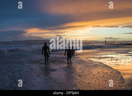 Surfers walking along the seashore at sunset on Boscombe beach in Dorset, England, UK - Stock Photo