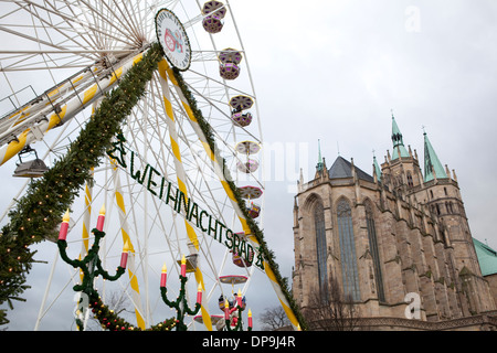 German Christmas Market in Erfurt, Germany with a ferris wheel in the foreground and St Mary's Cathedral in the - Stock Photo