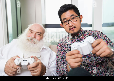 Portrait of grandson playing video game at home - Stock Photo