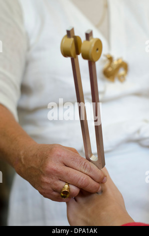 Close up of practitioner giving healing tuning fork treatment. - Stock Photo