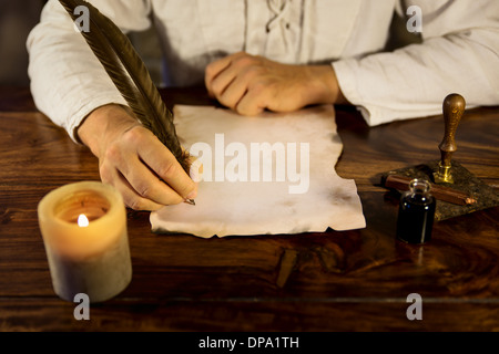 man writing on a old parchment - Stock Photo