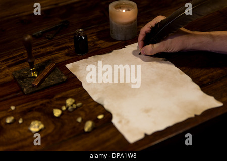 man writing with a feather on a old parchment - Stock Photo