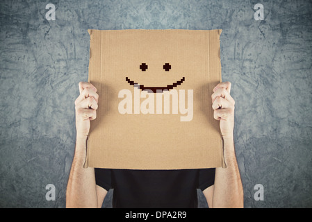Man holding cardboard paper with happy smiley face printed on. Happiness and joy concept. - Stock Photo