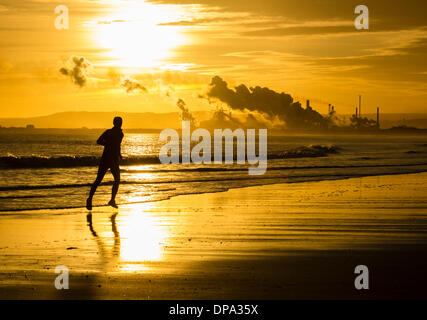 Man running on North Gare beach at sunrise.Redcar Steelworks in distance. Seaton Carew, England. UK - Stock Photo