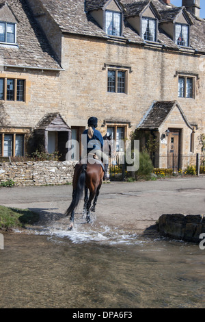A horse rider in the Cotswolds village of Lower Slaughter riding across the ford. The River Eye runs through the - Stock Photo