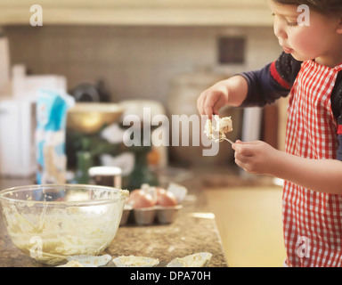 Child holding spoon with cake mix - Stock Photo