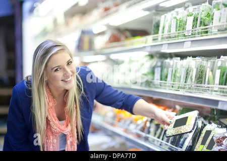 Young women looking at herbs in supermarket - Stock Photo