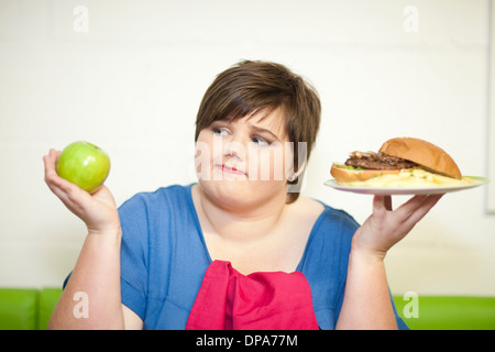 Young woman choosing between an apple and a burger - Stock Photo