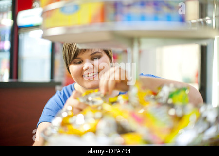 Young woman selecting confectionary in cafe - Stock Photo