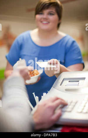 Young woman paying for takeaway order in cafe - Stock Photo