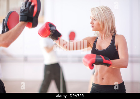 Young woman and trainer boxing in gym - Stock Photo
