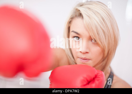 Portrait of young woman wearing boxing gloves - Stock Photo