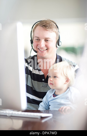 Father with baby boy using computer - Stock Photo