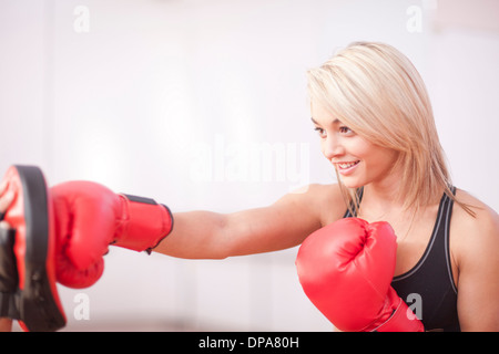 Young female training in boxing gloves - Stock Photo