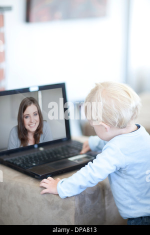 Baby boy distracted on video call to mother - Stock Photo