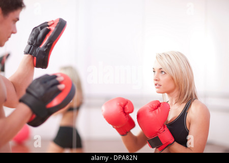 Young woman wearing boxing gloves in gym - Stock Photo